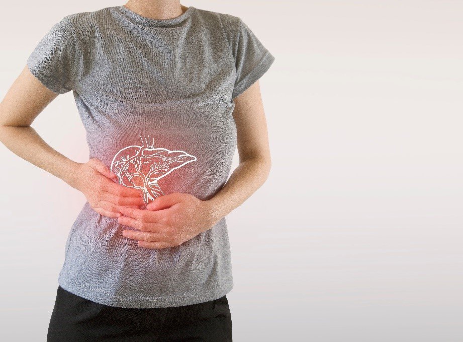 A woman holding her stomach representing her fatty liver